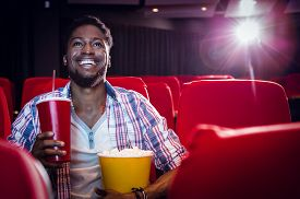 picture of cinema auditorium  - Happy young man watching a film at the cinema - JPG