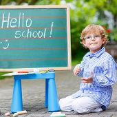 Cute Little Kid Boy With Glasses At Blackboard Practicing Writing poster