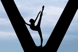 stock photo of ballerina  - Silhouette of a graceful ballerina in a black bathing suit that makes choreographic exercise in imaginative in support of the bridge against the backdrop of an overcast sky - JPG