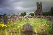 stock photo of irish moss  - Irish graveyard at Dingle peninsula old ruins of church long exposure gives moody feel caused by blurry vegetation and clouds - JPG