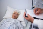 Doctor writing medical details of a senior patient in hospital poster