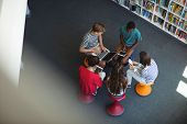 Overhead view of students using laptop, mobile phone, digital tablet in library at school poster