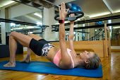 Fit woman exercising with pilates ring on mat in fitness studio poster