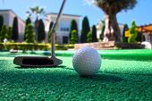 Mini golf scene with ball and club. Sunny day at resort park poster