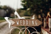 Beautiful White Shoes On Wooden Arrow With Wedding Text Sign. Rustic Wedding Concept. Pointing For W poster