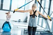 Blonde Fitness Woman Training With Trx Fitness Straps poster