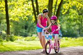Mother Teaching Child To Ride A Bike poster