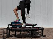 Mini Trampoline Workout: Girl Doing Fitness Exercise In Class At Gym poster