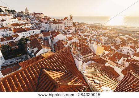 poster of Sunrise Over Lisbon Old Town Alfama - Portugal. Lisbon Golden Hour Skyline. Sun Rising Over Tagus Ri
