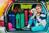 Summer vacation, young girl in car trunk with dog in the car is ready for travel for family vacation poster