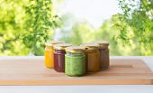 baby food, healthy eating and nutrition concept - vegetable or fruit puree in glass jars on wooden t poster