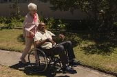 Front view of senior woman pushing senior man in a wheelchair on sunny day at park poster