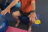 Low section of senior man exercising on exercise ball in fitness studio poster