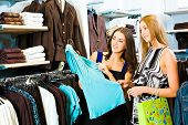 foto of shopping center  - Photo of two girls in the clothing store holding a blue dress and looking at it with smiles on the background of different clothes - JPG