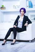 Elegant businesswoman with purple hair and elegant suit at the office. Contemporary business. poster