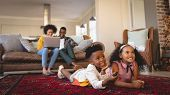Side view of happy African American sibling lying on floor and watching television while parents usi poster