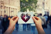 Health And Wellbeing Global Issue As Human Hands Holding A Paper Sheet With Heart And Cross Icon Ove poster