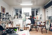 Painter Sits On A Chair In A Cozy Studio And Works On A Painting, Drawing Oil Paintings. Artist Work poster