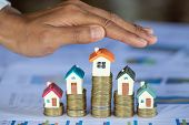 Hands As A Protecting Roof Over A Little House, Property Insurance And Security Concept. Protecting  poster