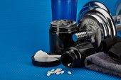 Sports  nutrition (supplements), dumbbells and sports accessories on a blue background. Fitness, bod poster