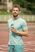 Man With Athletic Appearance Holds Bottle With Water. Athlete Drink Water After Training At Stadium  poster