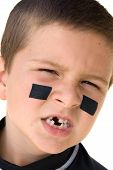 stock photo of missing teeth  - A young boy getting reaqdy to play hockey snarls at the camera to show off his missing teeth - JPG