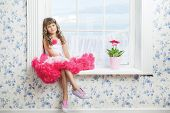 Romantic Dreaming Young Girl Sitting On Windowsill Near Flower