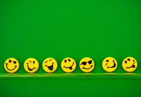 pic of smiley face  - Row of happy faces on green background happy faces - JPG