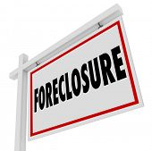 Foreclosure word on a home for sale real estate sign to illustrate failure to pay mortgage and defau