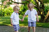 Two Little Sibling Boys Having Fun Outdoors In Family Look
