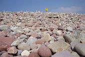 stock photo of lifeline  - Pink Pebbles and rocks beach of Mulrany in Ireland Europe on blue sky background with yellow lifeline - JPG