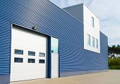 stock photo of roller door  - exterior of a modern warehouse with office unit - JPG