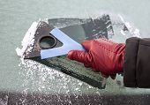 foto of ice-scraper  - Picture of a hand holding window scraper and removing ice of the car window