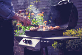 picture of braai  - Man is Cooking Meat On a Barbecue - JPG