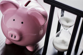 picture of pass-time  - Pink ceramic piggy bank with an hour glass conceptual of time running out to save for your retirement a nest egg or to meet your dreams - JPG