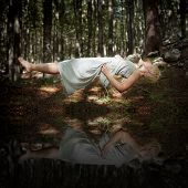stock photo of levitation  - Levitating woman in the forest above water - JPG