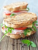 foto of deli  - Grilled deli sandwiches with ham and cheese on top of a chopping board - JPG