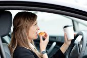 stock photo of coffee-cup  - Charming businesswoman eating and holding a drinking cup while driving to work - JPG