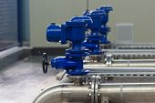 stock photo of hydraulics  - Industrial pipes and valves in water distribution process.