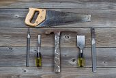 picture of chisel  - Top view of basic used tools on rustic wooden boards consisting of hammer metal files hand saw and chisels - JPG