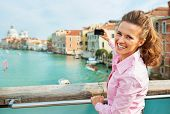stock photo of piccolo  - Happy young woman standing on bridge with grand canal view in venice italy and taking photo - JPG