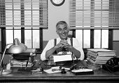 picture of 1950s style  - Smiling reporter working at office desk with vintage typewriter 1950s style - JPG