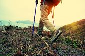 picture of woman boots  - one woman hiker hiking on seaside trail