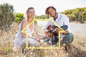stock photo of serenade  - Handsome man serenading his girlfriend with guitar against house outline - JPG