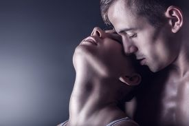 foto of hand kiss  - Kissing young couple on a dark background - JPG