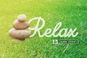 picture of relaxing  - Relax and slow down motivational inspiring quote with balance zen stones and green grass background ideal for spa and wellness poster - JPG