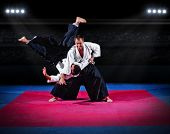 foto of aikido  - Fight between two aikido fighters at sport hall - JPG