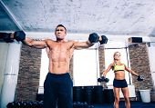 image of lifted  - Muscular man and fit woman lifting dumbbells at gym - JPG