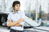 image of showrooms  - Handsome young man standing besides car in showroom  - JPG