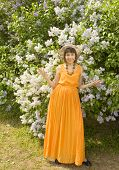stock photo of orange blossom  - Pretty European woman in orange summer dress and hat brunette standing near big lilas shrub in blossom.